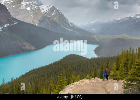 Zwei Personen sind Peyto Lake an einem kalten und verschneiten Tag im Sommer mit Blick auf. Banff Nationalpark, - Stockfoto