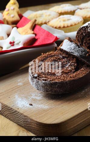 Ein süßes Weihnachten Dessert buffet auf Holztisch mit Schoko Yule Log, Kekse und Mince Pies im Hintergrund geprägt. - Stockfoto
