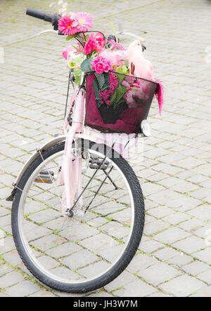 KEMPTEN, Deutschland - Juni 9: Rosa Fahrrad mit Blumen- und Papagei Deco in den Fahrradkorb in Kepmten, Deutschland - Stockfoto
