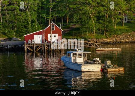 Hummer-Boot vertäut am Schwimmsteg in der Nähe von einer Hummer-Hütte in New Harbor, Maine, USA. - Stockfoto