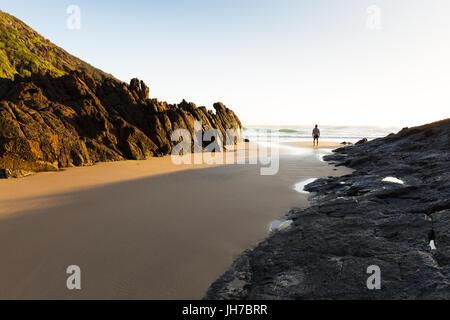 Eine Person steht allein an einem einsamen Strand in Australien und sieht die helle Morgensonne leuchten die Küste - Stockfoto