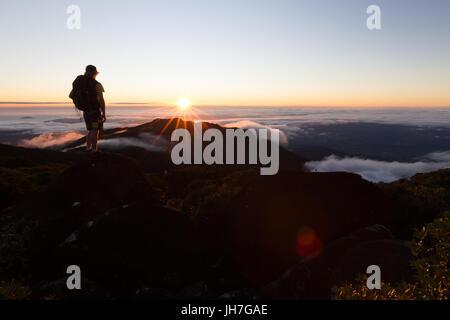 Ein Wanderer Uhren einen wunderschönen Sonnenaufgang auf vom Gipfel eines Berges über den Wolken in Australien. - Stockfoto