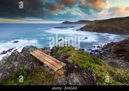 Eine leere Holzbank mit Blick auf eine schöne Felsküste bei Sonnenuntergang in Australien. - Stockfoto