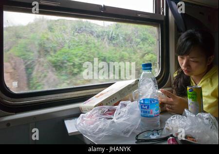 Die jungen chinesischen Frau im Zug auf Smartphone mit Tabelle der Snack essen und trinken vor ihr. Yunnan, China - Stockfoto
