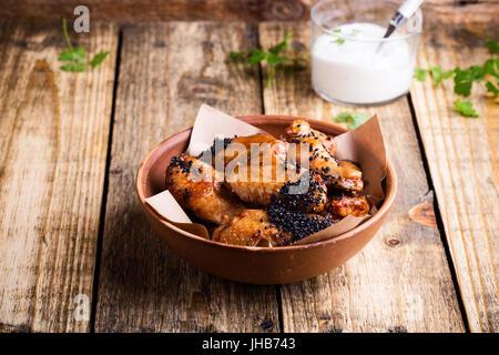 Würzige Hähnchenflügel mit Sesam in Keramikschale serviert mit Joghurt-Dip auf rustikalen Holztisch glasiert - Stockfoto