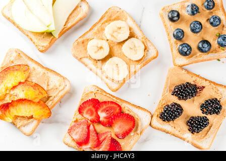 Traditionelle amerikanische und europäische Sommer Frühstück: Brötchen, Toast mit Erdnussbutter, Beeren, Obst Apfel, - Stockfoto