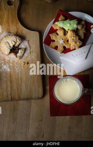 Overhead Schuss auf Holztisch Kekse (Cookies), Milch und Mince Pies, ausgelassen am Heiligabend für Santa, mit Liste - Stockfoto