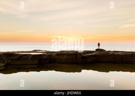 Eine Silhouette Person Uhren den Sonnenaufgang über dem Meer auf einer wunderschönen Küste in Australien. - Stockfoto