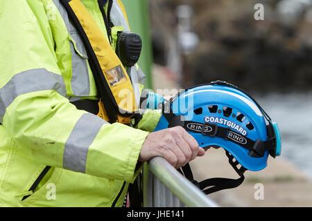 Britische Küstenwache Offizier, der Inhaber Helm, Schwimmweste und Radio - Stockfoto
