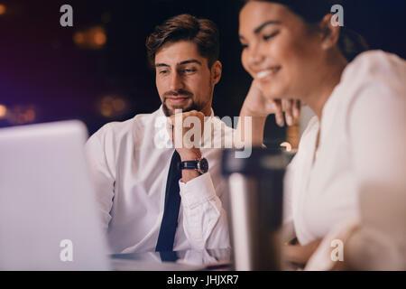 Business-Mann und Frau am Tisch sitzen und mit Blick auf Laptop. Geschäftsleute, warten am Flughafen-Lounge mit - Stockfoto