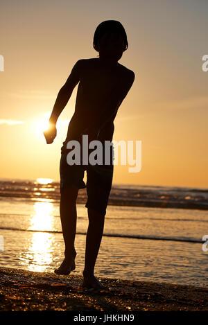 Silhouette von einem Kind am Strand bei Sonnenuntergang - Stockfoto
