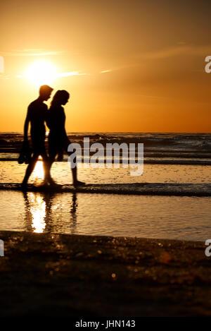 Silhouetten von ein paar walking am Strand bei Sonnenuntergang an der belgischen Küste - Stockfoto