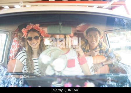 Porträt der happy Friends Zusammensitzen im Wohnmobil durch die Windschutzscheibe sehen - Stockfoto