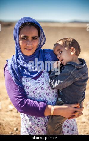 Porträt der Frau umarmt ihr Kind in der Nähe von Merzouga, Marokko - Stockfoto
