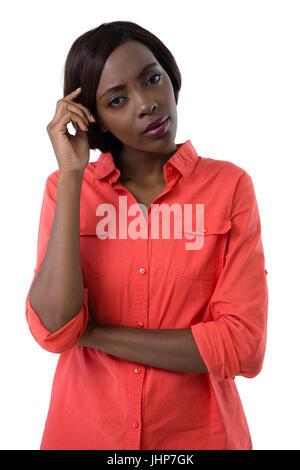 Porträt der jungen Frau mit Hand im Haar stehen vor weißem Hintergrund - Stockfoto