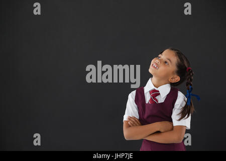 Nachdenklich Schulmädchen stehend gegen die Tafel im Klassenzimmer - Stockfoto