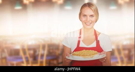 Porträt des Besitzers mit süßen Kuchen Platte gegen Café mit Tischen und Stühlen - Stockfoto