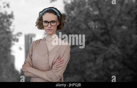 Porträt von zuversichtlich, schöne junge Frau mit Armen gekreuzt gegen Türme durch Bäume in der Stadt gesehen - Stockfoto