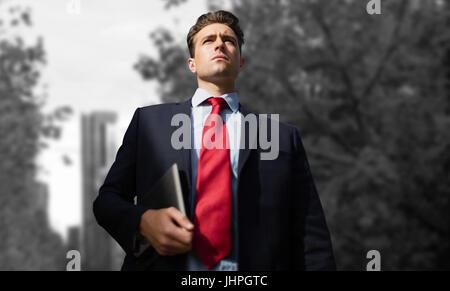 Niedrigen Winkel Ansicht der Geschäftsmann mit digital-Tablette gegen Türme durch Bäume in der Stadt gesehen - Stockfoto