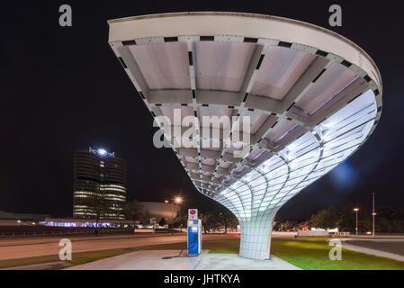 Futuristische Architektur des ein elektrisches Ladegerät für Elektro-Autos vor der beleuchteten Fassade der BMW - Stockfoto
