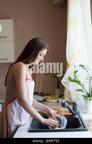 Mädchen Hausfrau wäscht schmutzige Geschirr in der Küche - Stockfoto