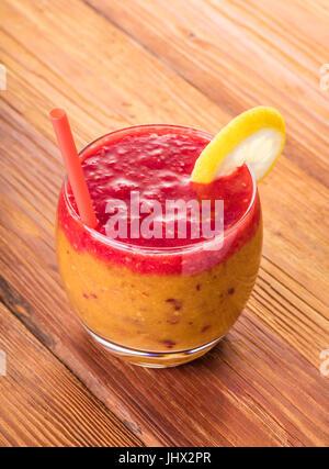 Frucht-Cocktail im Glas mit einem Strohhalm, Pfirsich und Himbeere - Stockfoto