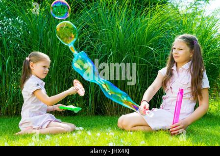Kinder spielen mit Seifenblase Zauberstab im Park an einem sonnigen Sommertag - Stockfoto