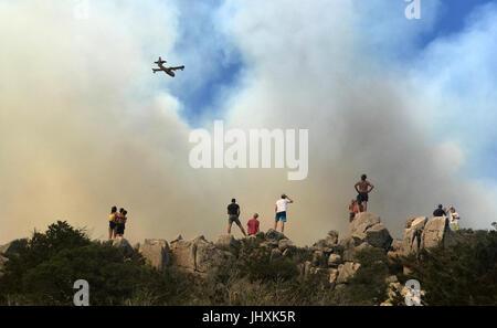 Korsika, Frankreich. 17. Juli 2017. Leute zu beobachten eine Brandbekämpfung Flugzeug fliegen in Richtung Wald Feuer, - Stockfoto