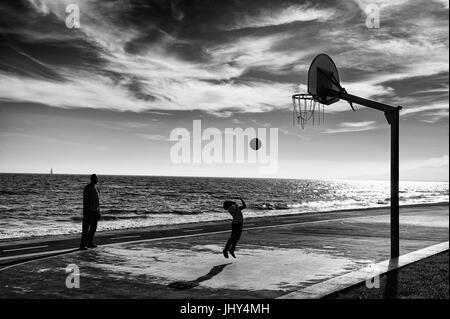 Vater beobachtete seinen kleinen Jungen versuchen, einen Ball werfen bis zu den Korb in Cambrils, Spanien - Stockfoto