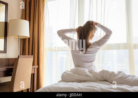 Reife Frau erwacht in ihrem Schlafzimmer in einem Hotel/apartment - Stockfoto