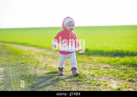 Glückliche kleine Mädchen zu Fuß auf der Wiese und Blick auf Sonne - Stockfoto