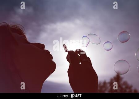 Niedrigen Winkel Nahaufnahme Blick auf die Silhouette einer Frau bläst Seifenblasen vor einem sonnigen blauen Himmel. Stockfoto