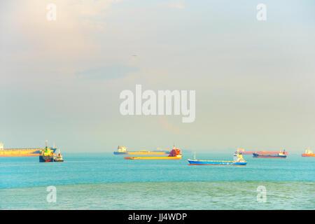 Flugzeug fliegen über die gewerbliche Schifffahrt Tanker im Hafen von Singapur - Stockfoto