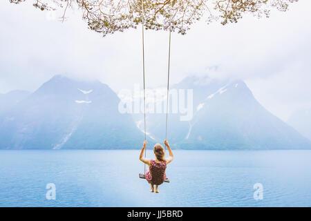 Traum Konzept, schöne junge Frau auf der Schaukel in Fjord Norwegen, inspirierende Landschaft - Stockfoto