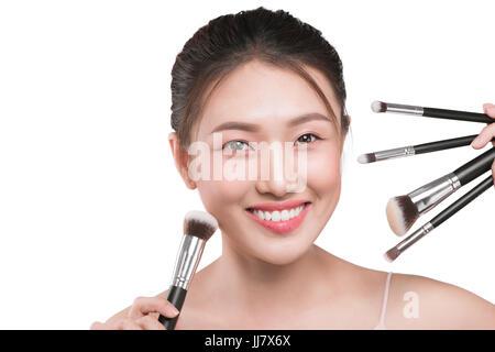 Schöne Frau mit kosmetischen Make-up-Tools in der Nähe von ihrem Gesicht. - Stockfoto