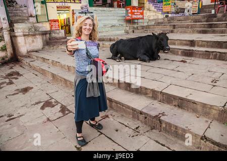 Eine weibliche Touristen die eine Handy Selfie mit einer ruhenden Kuh auf die Treppe hinunter in den Ganges in Varanasi, - Stockfoto