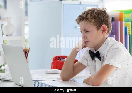 Geschäftsmann, arbeiten am Laptop beim Sitzen am Schreibtisch im Büro konzentriert - Stockfoto