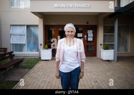 Porträt von lächelnden senior Frau stehend gegen Hauseingang - Stockfoto