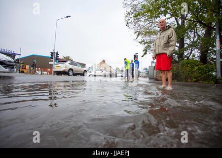 Menschen ertappt von sintflutartigen Regenfällen und Überschwemmungen während eines Sturms Sommer Spaziergang durch - Stockfoto