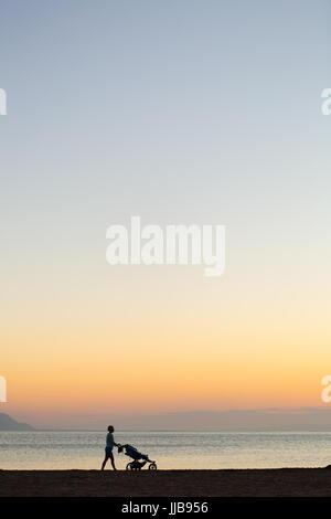 Silhouette der Mutter mit Kinderwagen Mutterschaft bei Sonnenuntergang Landschaft zu genießen. Walking oder jogging - Stockfoto