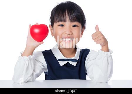 Asiatische chinesische Mädchen halten Rote Herzchen in isolierten weißen Hintergrund - Stockfoto