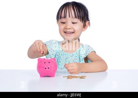 Asiatische chinesische Mädchen Sparschwein in isolierten weißen Hintergrund Münzen Inbetriebnahme - Stockfoto