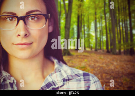 Porträt der jungen Frau mit Brille gegen Baumstämme im Wald hautnah