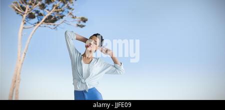 Schöne junge Frau, die gegen die Ansicht von einem Baum stehend - Stockfoto