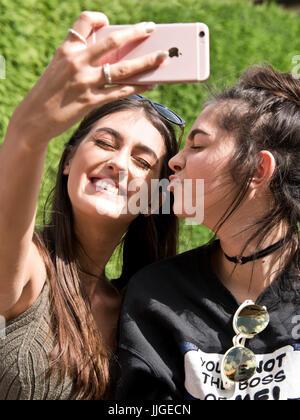 Vertikale Porträt von zwei Mädchen, die die Selfies auf ihrem Handy. - Stockfoto
