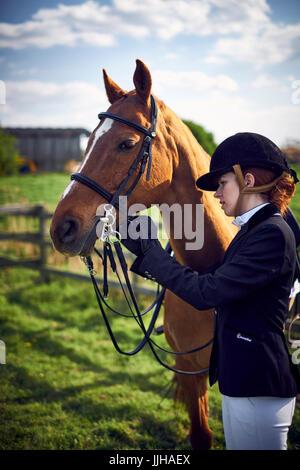 Eine junge Frau, die ihr Pferd vor einer Fahrt aufkreuzen. - Stockfoto