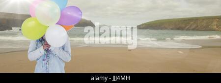 Frau Mittelteil mit Luftballons am Strand mit Flare 3d - Stockfoto