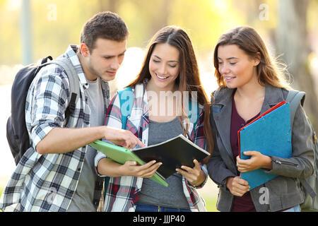 Vorderansicht der drei Studenten lernen ein Notebook lesen und kommentieren auf der Straße - Stockfoto