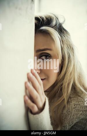 Angst junge Frau versteckt sich hinter der Wand auf der Suche nach Weinen - Stockfoto