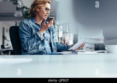 Junge Geschäftsfrau Lautsprecher telefonieren mit Dokument. Junge Frau sitzt im Büro mit Smartphone und mit Blick - Stockfoto